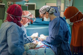 STS Member Dr. Kathleen Fenton (Nicaragua) assists a surgeon in Libya who is performing open heart surgery. Photo courtesy of the Novick Cardiac Alliance.